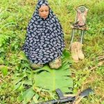 Female Nigerian Soldier Praying With Her Rifle At The Battlefield. Photo